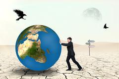 Businessman pushes world sphere - stock photo