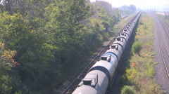 Long train of crude oil and chemical tankers rolling down the tracks Stock Footage
