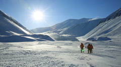 Skiers on the background of a snowy sunny landscape at Svalbard Norway Stock Footage