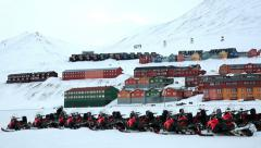 Many snowmobiles on the background of a small town in the far North. - stock footage