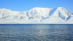 The waves of the Arctic Ocean and the snow-capped mountains of the Spitsbergen. - stock footage