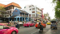 Cars, taxis and tuk-tuk queue in leftmost lane to enter or pass Khaosan road Stock Footage