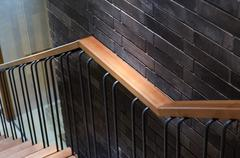 Wooden handrail with brick wall Stock Photos