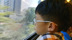 boy sits and looks out of window trains - stock footage