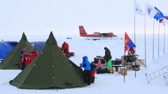 Members of polar expedition set up the tents and unpack the scientific equipment - stock footage
