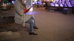 Cute woman in a coat using a tablet on the street at evening. Stock Footage