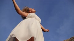 Pretty Airy Angel Girl in White Dress against Blue Sky Stock Footage