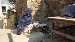 Village woman making bread near cow dung Stock Footage