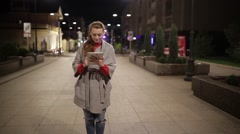 Young girl in a coat is on the boulevard and enjoys the tablet. Stock Footage