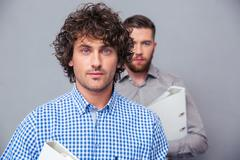 Two serious businessmen holding folders - stock photo