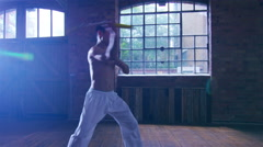 4K Young Asian martial artist training alone, practising his moves with nunchaku Stock Footage