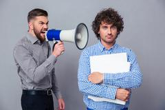 Businessman screaming via megaphone to another man Stock Photos