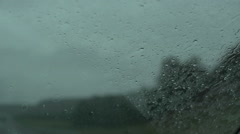 POV rain droplets on car window driving with windshield wipers Stock Footage