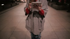 Young girl working in a coat with a tablet on the street at night. Stock Footage