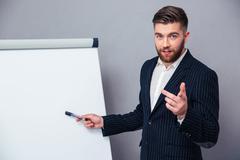 Businessman presenting something on blank board - stock photo