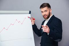 Businessman presenting something on board - stock photo