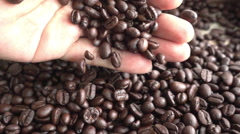 Roasted coffee beans falling from man hand, slow motion Stock Footage