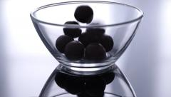 Round chocolate candies falling down in a glass bowl Stock Footage