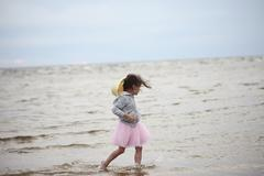 Little girl walking in waves against sea and sky - stock photo