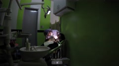 Dentist cleaning young man's teeth Stock Footage