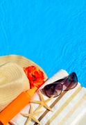 Beach hat, sunglasses, bath towel, sun spray, starfish near - stock photo