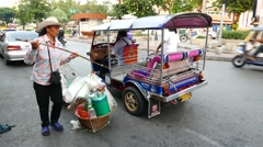 Asian woman pack shoulder pole and large baskets into tuk-tuk, go away Stock Footage