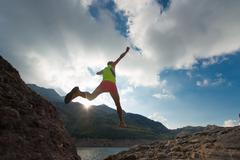 Skipping girl as he runs in the mountains - stock photo