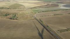 Stock Video Footage of the shadow of the wind generator working in the field (shooting from the air)