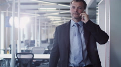 Businessman on the Phone in Walking through Office Stock Footage