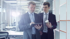 Two Businessmen are Walking Through Office. Office Worker Holding Tablet PC. Stock Footage
