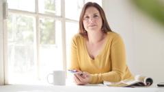 Caucasian brunette sitting, desk, window, talking and smiling Stock Video 4K - stock footage