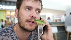Man eating chewing vegetable healthy salad during talking on the cell phone Stock Footage