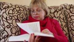 Woman sitting on a couch flipping through the pages of a big book Stock Footage