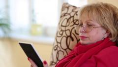 Woman sitting on a couch and reading electronic book. Woman with e-book Stock Footage