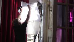 Illuminator installs a light fixture on the set of the film. Film shooting - stock footage