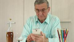Man with smartphone sits at a table Stock Footage