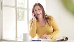 Happy caucasian brunette sitting, desk, window, phone, laughing Stock Video 4K - stock footage