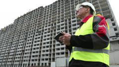 Master builder with tablet PC at construction site Stock Footage