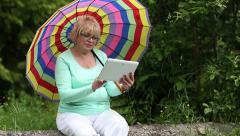 Woman sits on a fallen tree and uses tablet PC Stock Footage