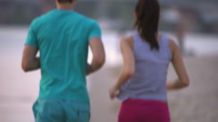The couple (pair) run on the beach by river and bridge backround - stock footage