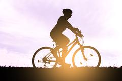Silhouette of the cyclist at dawn. - stock photo
