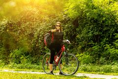 Happy Young Woman riding bicycle - stock photo