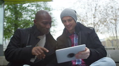 4K Casual male friends outdoors in the city using computer tablet for navigation Stock Footage