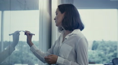 Young Female Office Worker in White Shirt is Writing on Glass Whiteboard. Stock Footage