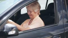 New Car: Senior attractive woman win or buy a new modern car and joy Stock Footage