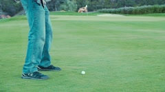 Slow motion of a man hitting the golf ball with his golf club on course Stock Footage