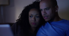 An attractive couple watching a scary movie on their laptop. Shot on RED Epic. Stock Footage
