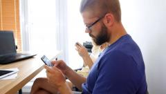 Two young people sitting behind the table and using their mobile phones Stock Footage