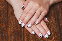 Black and white  nail art on wooden background - stock photo