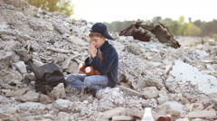 Dirty little orphan boy sits and reads a prayer with folded hands against the Stock Footage